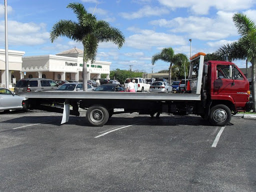 Flatbed tow truck in front of Flanigans in Boca Raton